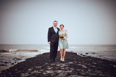 Brautpaar gemeinsam auf Buhne am Strand